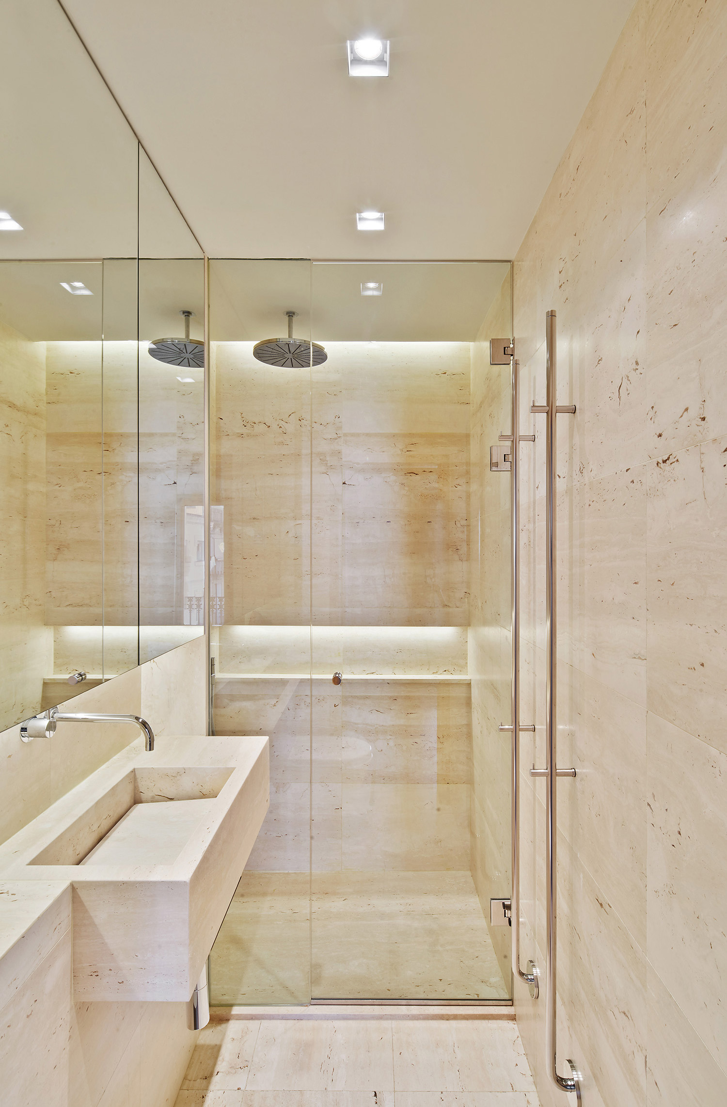 Barcelona apartment renovation with travertine stone bathroom and mirror cabinets